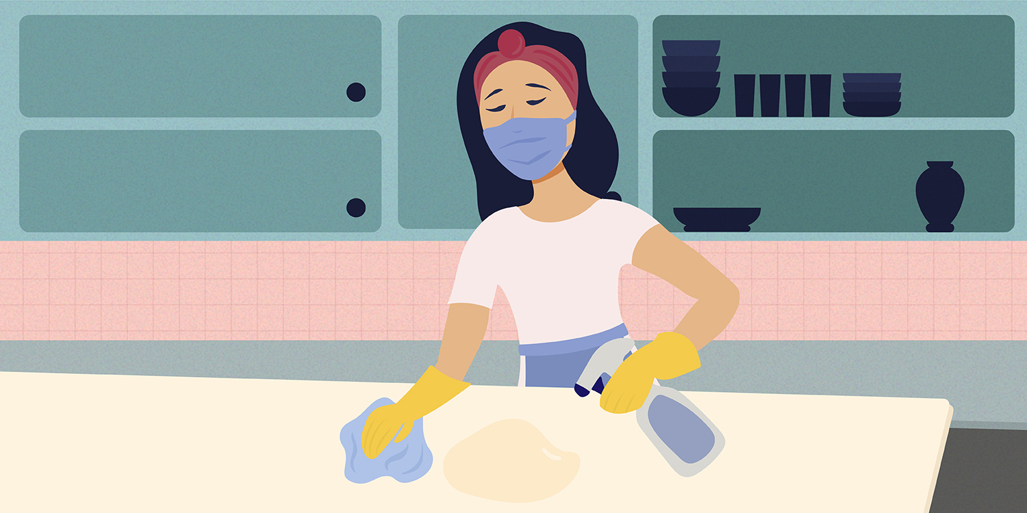 This picture shows a woman in a facemask standing in a kitchen cleaning a countertop.